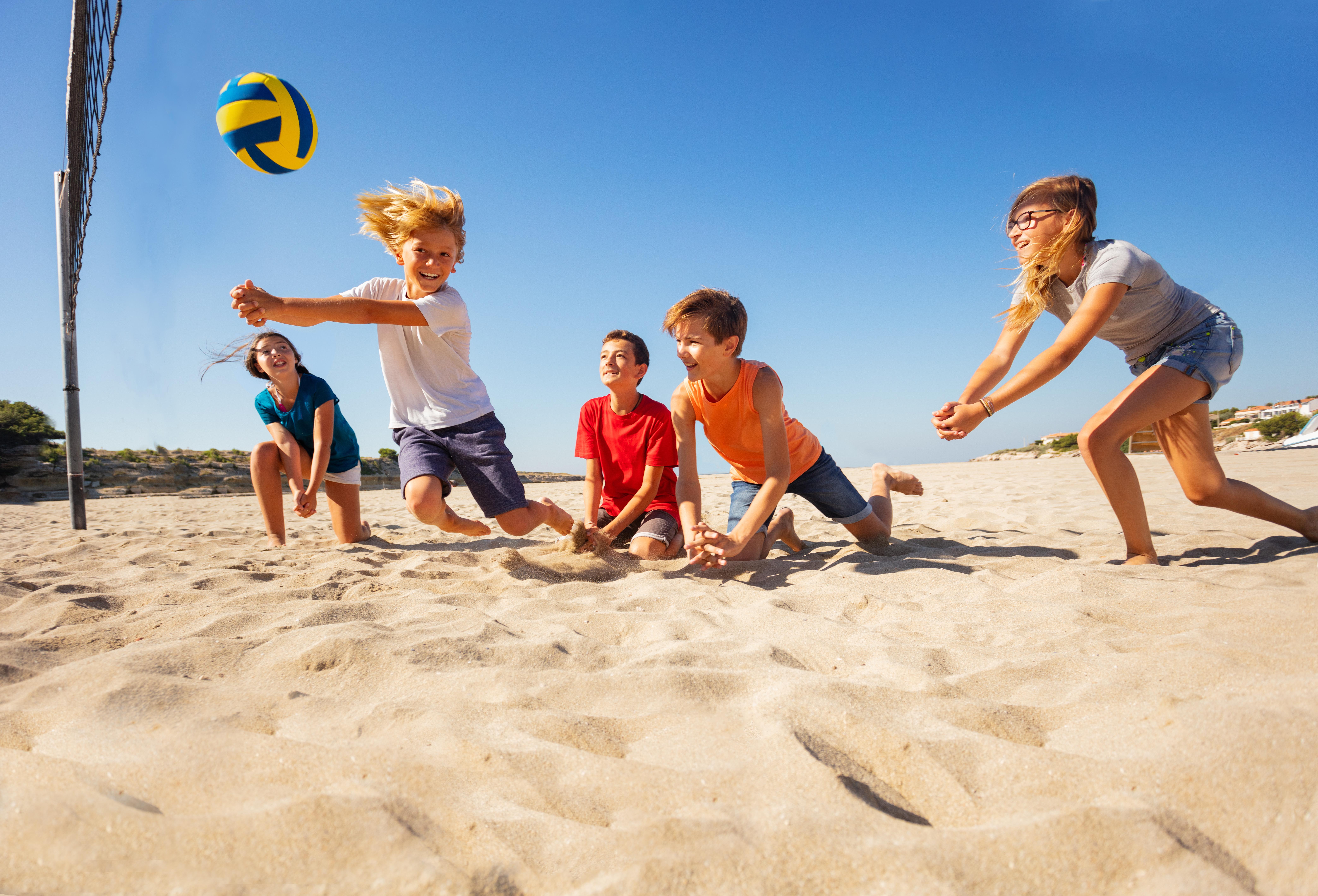 Jongens volleyballen op het strand